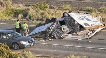 Buy this photo at Photos.YumaSun.com PHOTO BY CRAIG FRY/YUMA SUN Officers from the Department of Public Safety look at an overturned travel trailer blocking both East bound lanes of travel on Interstate 8 near mile marker three Tuesday morning as traffic passes by in the emergency lane. The cause of the accident is under investigation and No injuries were reported from the scene.